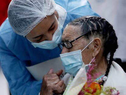 Joaquina Garzón, de 92 años, lleva un ramo de flores mientras usa una mascarilla, durante su alta del Hospital Suesca donde se recuperó de la covid-19 en Suesca, Colombia, 23 de abril de 2020.