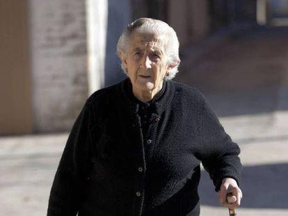 Una anciana pasea por la calle.