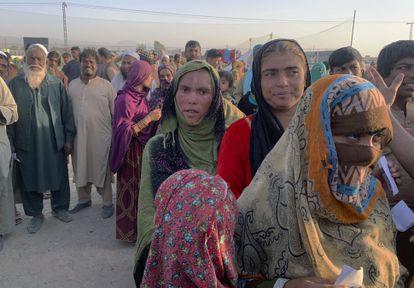 Familias afganas hacen cola para recibir alimentos de una ONG en las afueras de la ciudad paquistaní de Chaman, en la frontera con Afganistán, el 31 de agosto.
