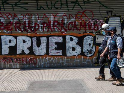 Dos personas caminan en Santiago de Chile delante de una pintada que llama a votar por la reforma constitucional el próximo domingo, en Santiago de Chile.