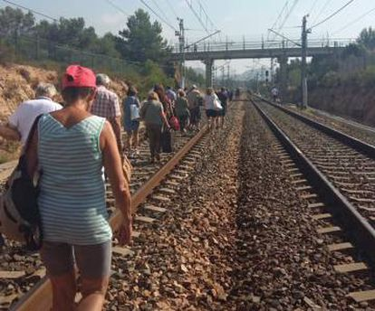 Pasajeros de un tren afectado caminan por las vías.