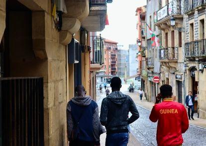 Tres jóvenes recorren el camino desde el albergue de Cruz Roja de Irún hasta la Plaza del Ayuntamiento en julio de 2021.