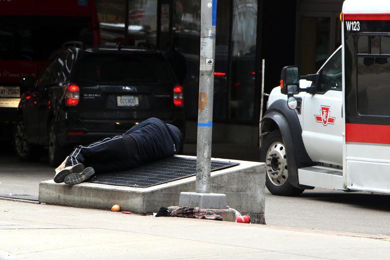 Una persona sin hogar duerme este martes en la salida del Hospital General de Toronto, en Canadá.