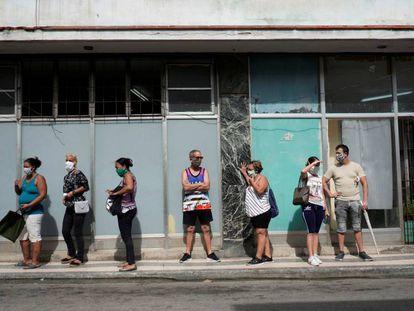Un grupo de personas hace cola para comprar comida en La Habana (Cuba).