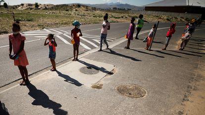 Niños hacen cola para recibir comida en un plan de alimentación escolar durante un cierre nacional destinado a frenar la propagación de la covid-19 en Blue Downs, cerca de Ciudad del Cabo, Sudáfrica, 4 de mayo de 2020.