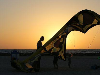 Un hombre y sus hijos preparan la vela de su kitesurf en Kite Beach en Dubái, Emiratos Árabes Unidos.