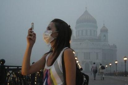 Un mujer toma una fotografía con su teléfono móvil en un Moscú cubierto por el humo.