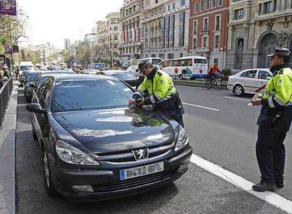 Agentes de tráfico denuncian los vehículos oficiales de la vicepresidenta y la ministra de Igualdad en la calle de Alcalá.