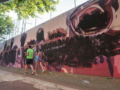 Un hombre y una mujer pasan este lunes por delante del mural vandalizado.