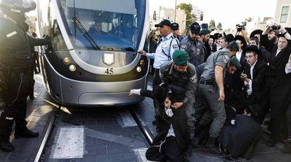 La policía dispersa a manifestantes ultraortodoxos que cortan el paso al tranvía en el centro de Jerusalén.