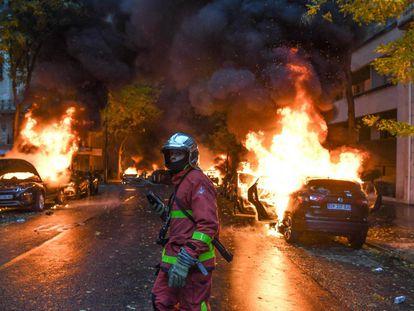 Un bombero junto a varios vehículos ardiendo en París.