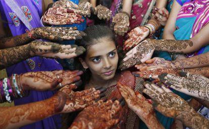 Un grupo de escolares muestran sus manos decoradas con henna en la ciudad india de Ahmedabad.