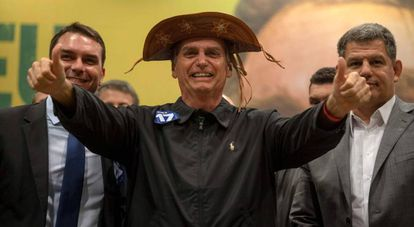 Jair Bolsonaro (c) en un acto junto a su hijo, el senadorFlavio Bolsonaro (i) y el presidente del PSL, Gustavo Bebianno, en Río de Janeiro.