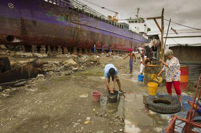 Varias personas recogen agua en Tacloban, una de las zonas más afectadas por el tifón Haiyan de 2013, en octubre de 2014.