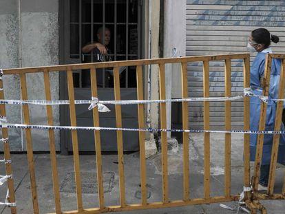 Una funcionaria del Ministerio de Salud conversa el pasado 5 de julio con un hombre que está bajo medidas sanitarias junto a otras 50 personas en un recinto de alquileres de habitaciones intervenido por las autoridades, en San José (Costa Rica), donde el día antes falleció una persona por Covid-19.