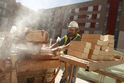 Un albañil corta unos ladrillos delante de una obra