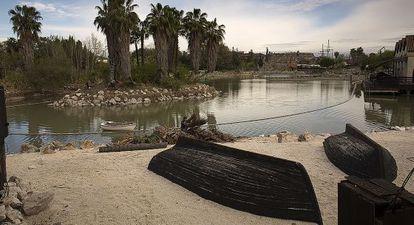 Un empleado de Isla Mágica limpia la zona del lago para la apertura prevista el próximo día 19 de abril.