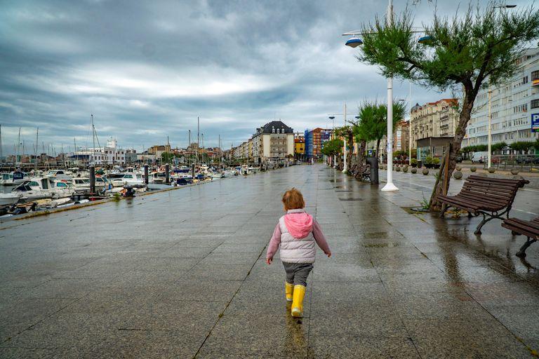Una niña pasea por Santander este viernes, a pesar de la lluvia esta mañana.