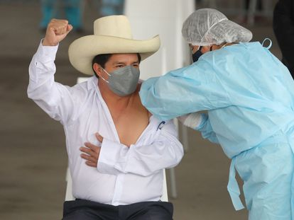Pedro Castillo levanta el puño mientras recibe la primera dosis de la vacuna el 6 de agosto.