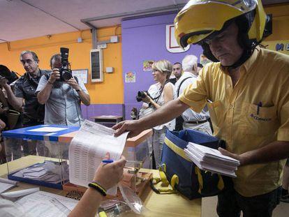 Un cartero trae a una mesa electoral el voto por correo en 2016.