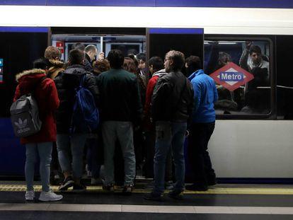 Decenas de viajeros tratan de entrar en un vagón del metro en la estación de Príncipe Pío.