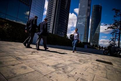 Varias personas pasean por la zona financiera de las cuatro torres en Madrid.