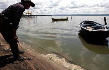 Un hombre observa el agua contaminada de la orilla del lago Ypacaraí en la localidad de Areguá (Paraguay). EFE/Archivo
