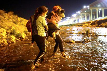 Dos madres con sus hijos en brazos cruzan el Río Bravo en Ciudad Juárez, el 30 de marzo de 2021.