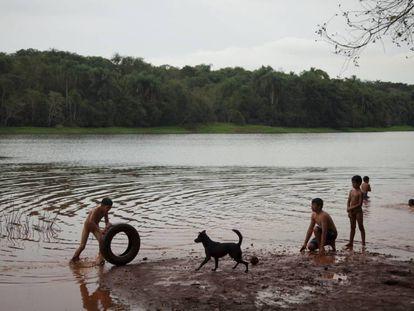Los niños nadan en el río Paraná, aunque la empresa Itaipú ha prohibido a la comunidad pescar en él.