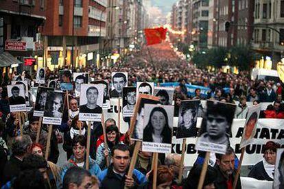 Familiares y amigos de presos etarras portan fotografías de éstos en la marcha de Bilbao.