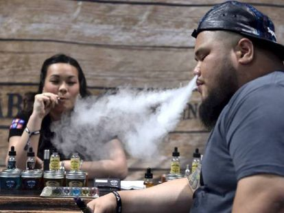 Dos personas fuman cigarrillos electrónicos en un encuentro para vapeadores en Las Vegas.