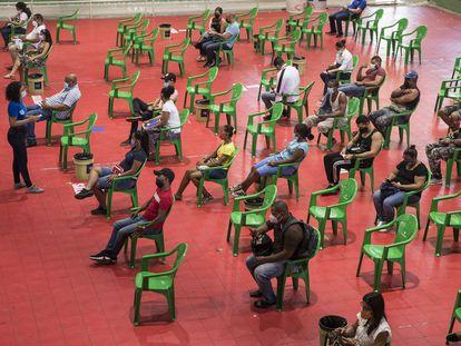 Varias personas esperan para recibir sus vacunas contra la covid-19 en el centro de vacunación del Centro Olímpico Juan Pablo Duarte en Santo Domingo, República Dominicana.