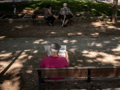 Un hombre lee EL PAÍS en un parque de Madrid.