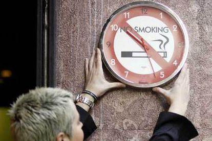 El tiempo corre para el tabaco en el trabajo. Una mujer coloca un reloj alusivo ayer en Bilbao.