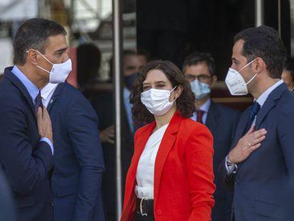 Isabel Díaz Ayuso, presidenta de la Comunidad de Madrid, flanqueada por el presidente del Gobierno, Pedro Sánchez (a la izquierda), y el vicepresidente de la Comunidad, Ignacio Aguado, el lunes.