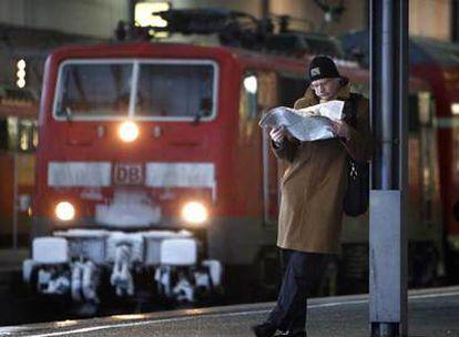 Un usuario del tren lee el periódico en la estación central de Múnich.