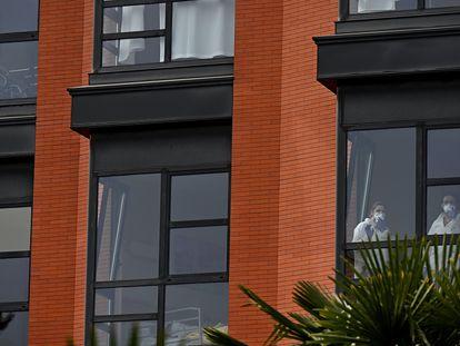 Varios trabajadores miran por la ventana desde el interior de la residencia de ancianos Monte Hermoso, este miércoles, en Madrid. EFE/Fernando Villar