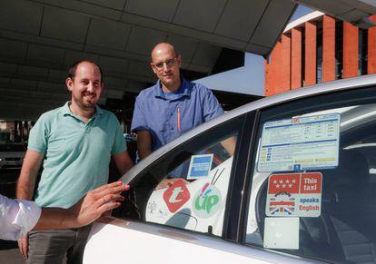 Los taxistas Daniel Elizo (izquierda) y Oscar López (derecha) posan en un taxi con la pegatina 'This taxi speaks English' que acredita su nivel básico de inglés.