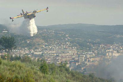 Un hidroavión intenta sofocar el fuego sobre una de las colinas junto a la ciudad de Ourense.