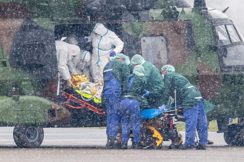Varios sanitarios transportan a un enfermo, en el aeropuerto de Mühlheim (Alemania) el domingo.