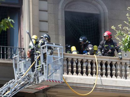 Bomberos extinguiendo el fuego del edificio.