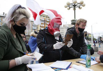 Activistas con guantes y mascarilla recogen firmas para los candidatos opositores en Minsk, el pasado domingo.