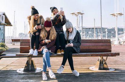Unas jóvenes con sus teléfonos móviles.