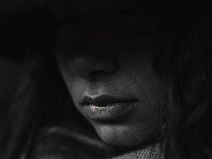 Imagen de una mujer triste en penumbra.