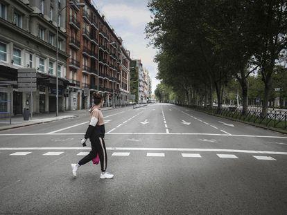 Una mujer cruzando un vacío Paseo del Prado de Madrid, durante el estado de alarma.