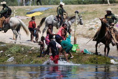 Agentes de la patrulla fronteriza de Estados Unidos cortan el paso a migrantes solicitantes de asilo que intentan regresar a Estados Unidos por el río Grande.