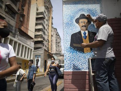 Venezuelan artist Mervin Marmol puts finishing touches on his painting of late Venezuelan Dr. Jose Gregorio Hernandez at the street corner where he died in a car accident in 1919 in La Pastora neighborhood in Caracas, Venezuela, Monday, April 26, 2021. Known as the