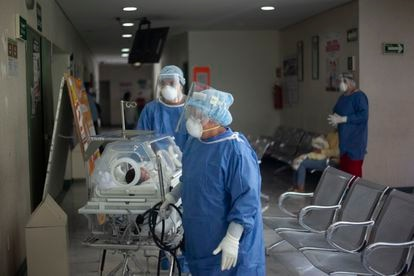 Trabajadores del área de la covid-19 trasladan a un bebé en un hospital en Ciudad de México.