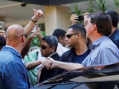 El presidente Bolsonaro estrecha la mano de un admirador este viernes en Brasilia.