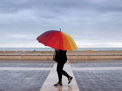 Una persona pasea por la playa de la Malvarrosa, en Valencia, protegida con un paraguas el domingo por la mañana.